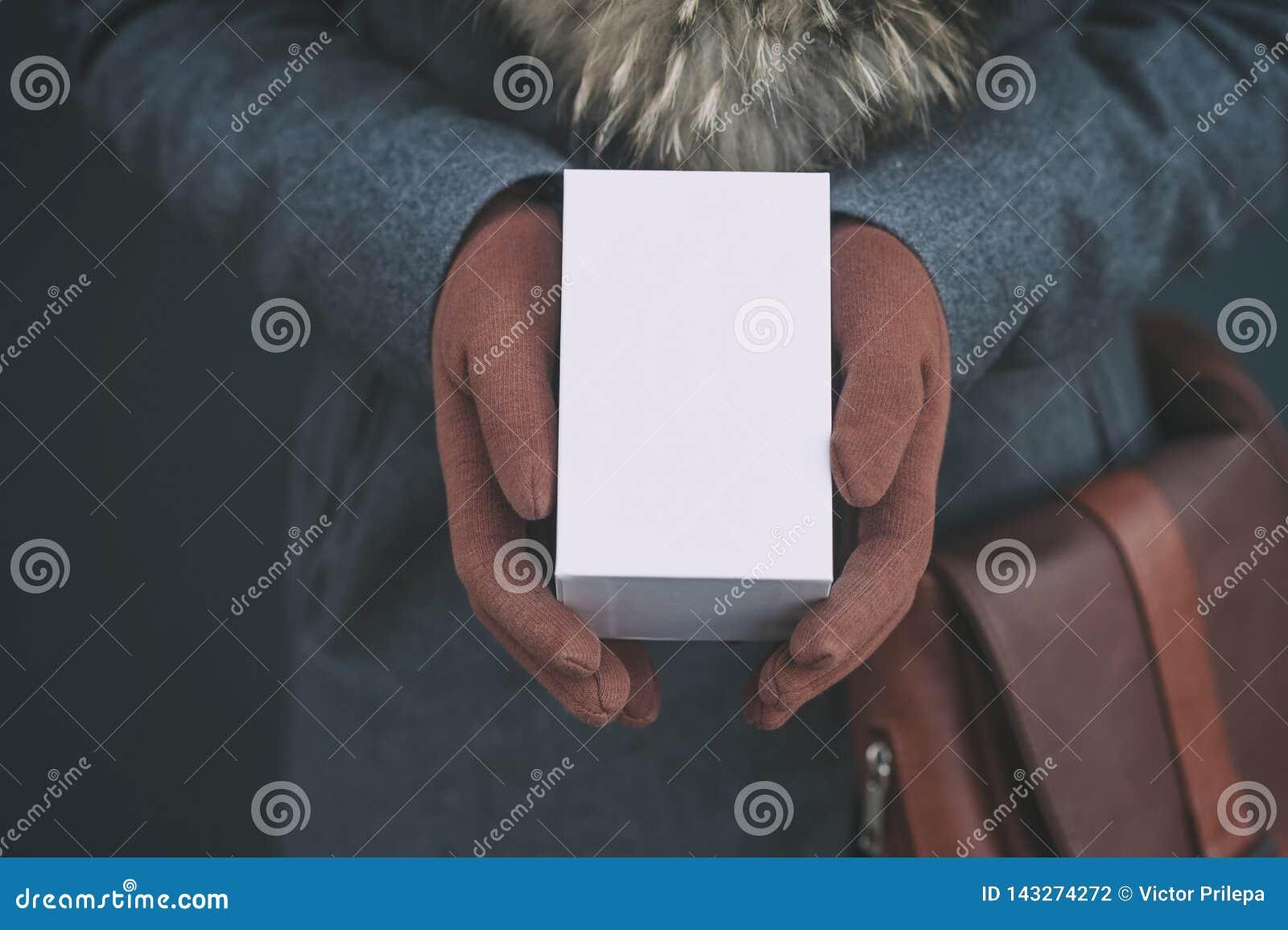 Derida su con la scatola bianca da uno smartphone La ragazza in un cappotto e nei guanti marroni tiene un regalo in sue mani