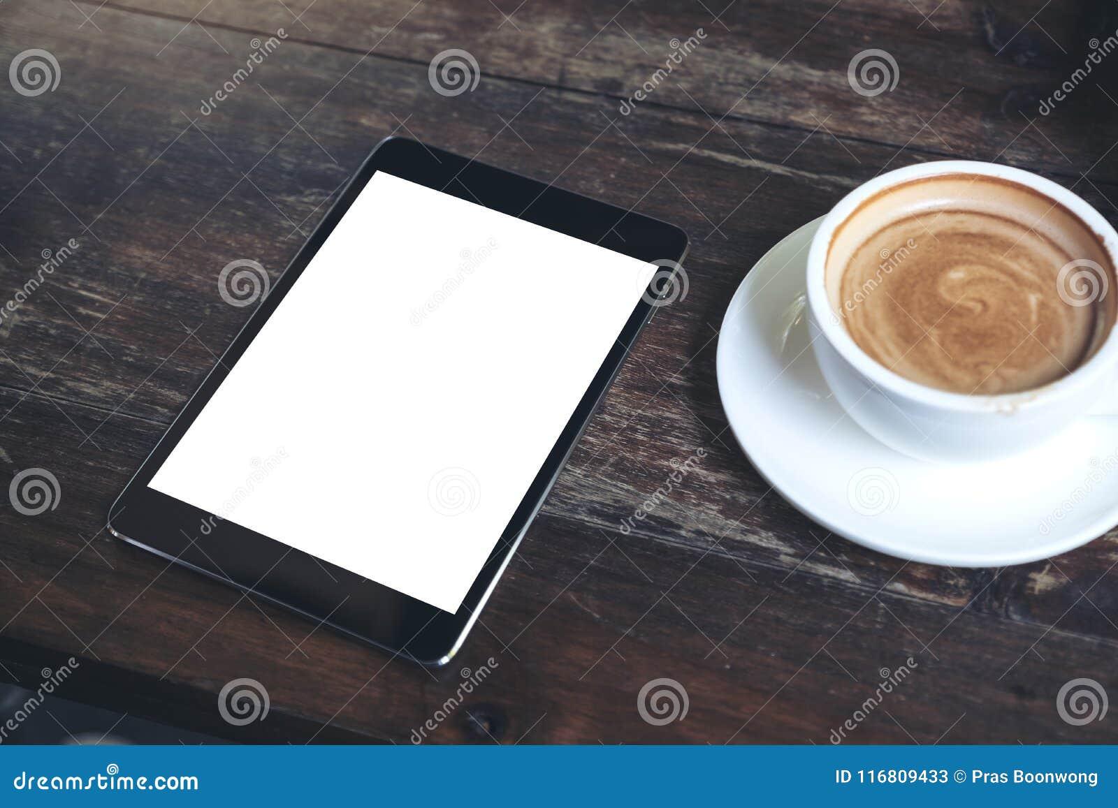 Derisione di vista superiore sull immagine della compressa nera con la tazza da tavolino in bianco bianca di caffè e dello scherm