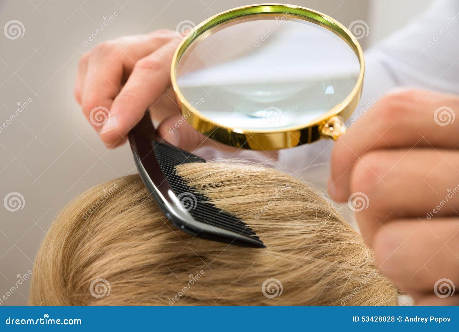 Dermatolog blondynki przyglądający włosy przez powiększać - szkło