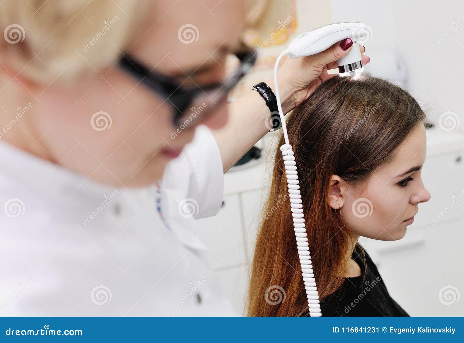 Dermatologe überprüft ein geduldiges Frauenhaar unter Verwendung eines speziellen Gerätes