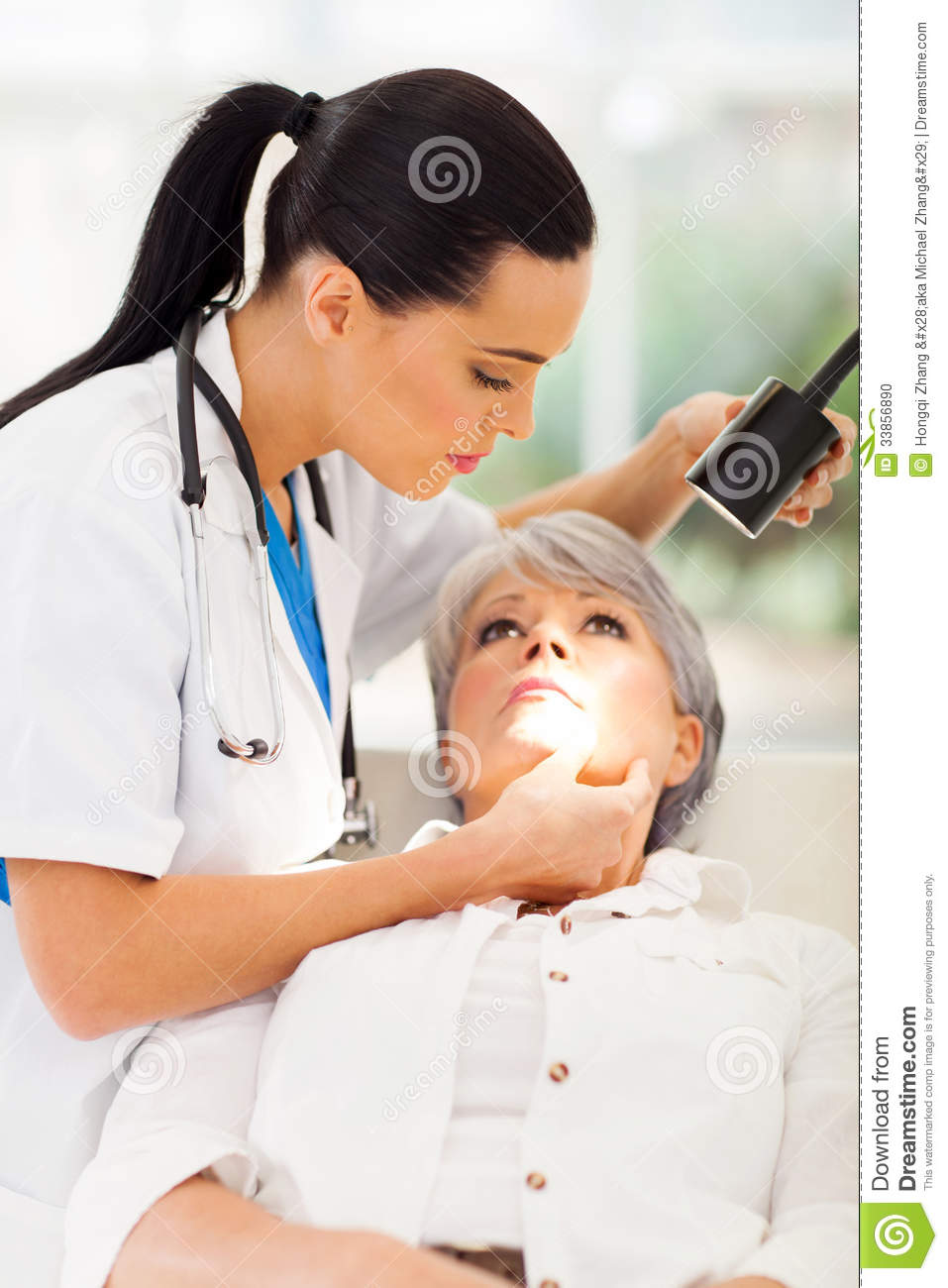 Beautiful dermatologist inspecting middle aged patient's skin in ...