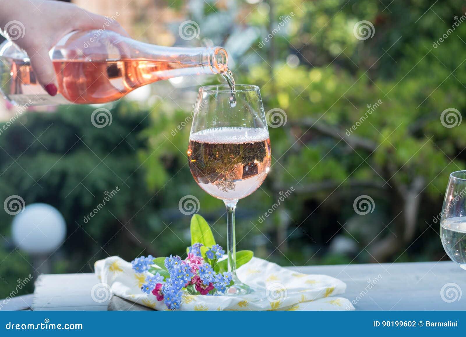 Derramamento do garçom glas do vinho cor-de-rosa frio, terrase exterior, ensolarado
