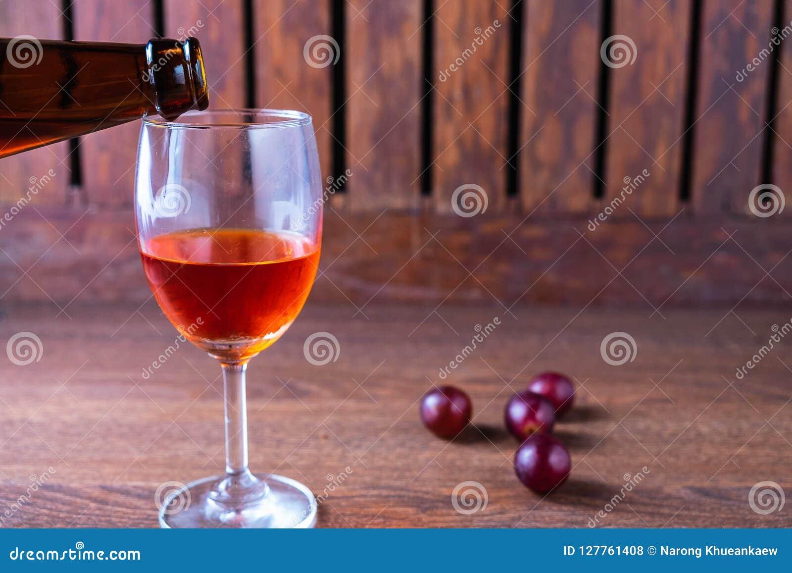 Derrame o vinho tinto em um vidro do vinho em um fundo de madeira