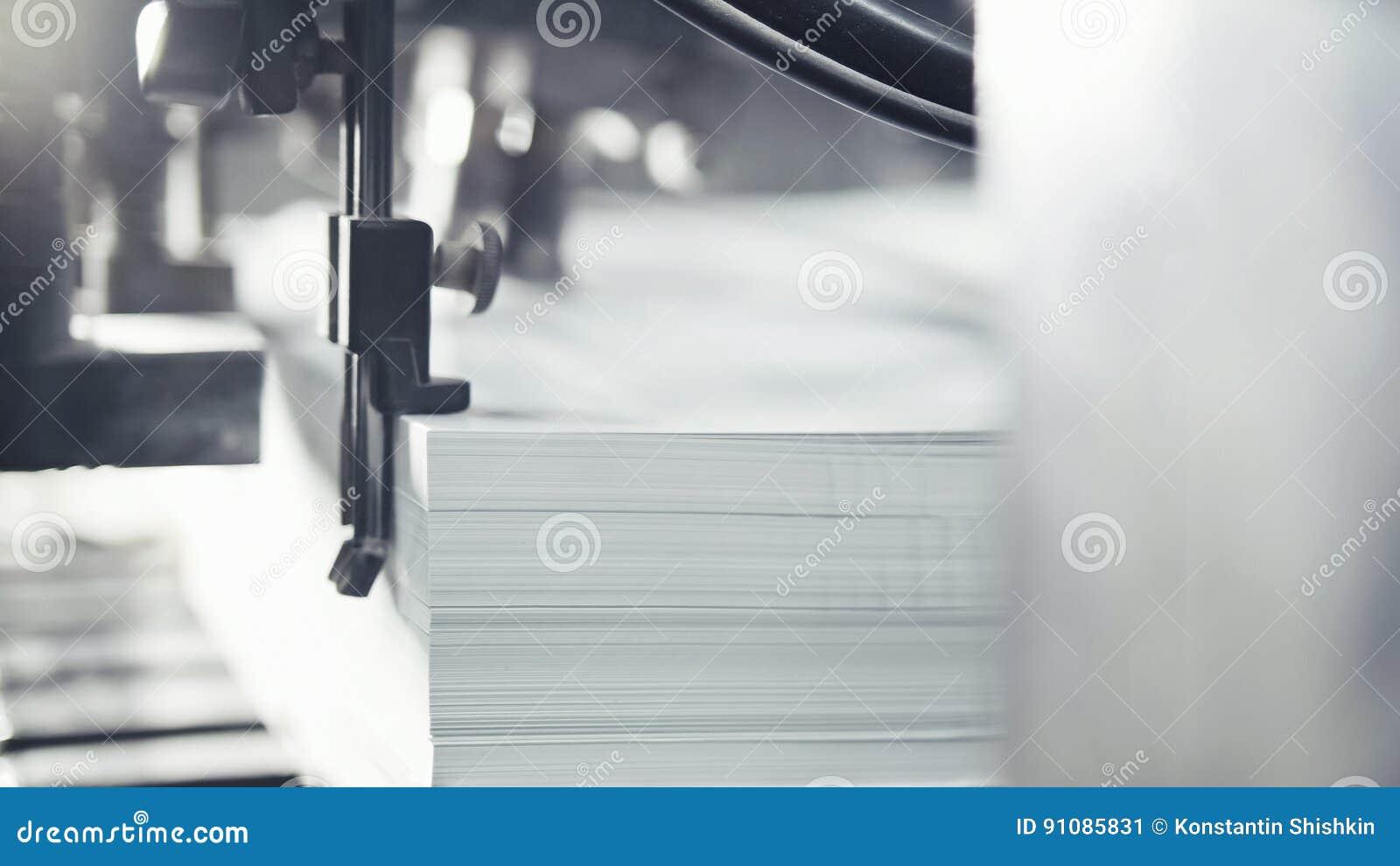 Des feuilles de papier imprimées sont servies dans la presse typographique Compensation, CMYK