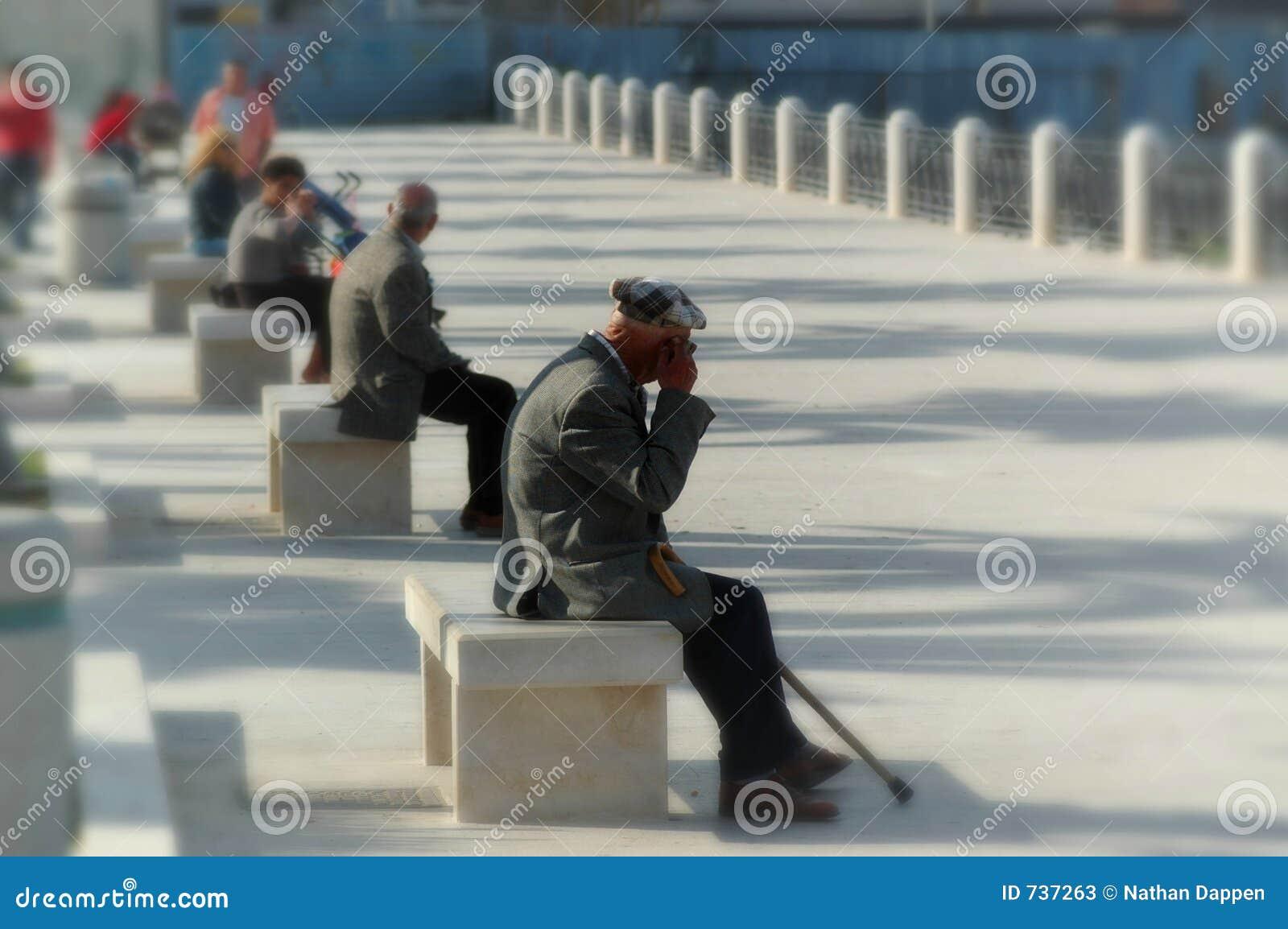 Des hommes plus âgés sur des bancs