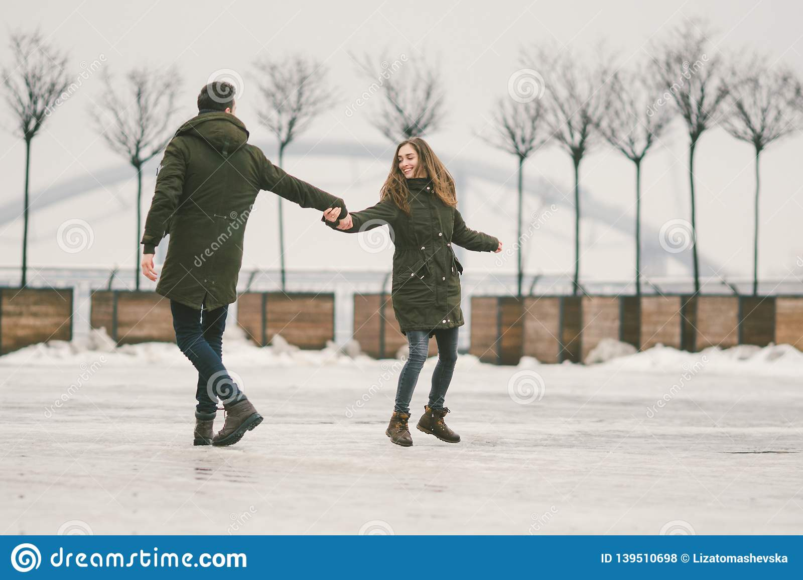 Des jeunes de couples hétérosexuels dans des étudiants d amour un homme et une femme caucasienne En hiver, dans la place de ville