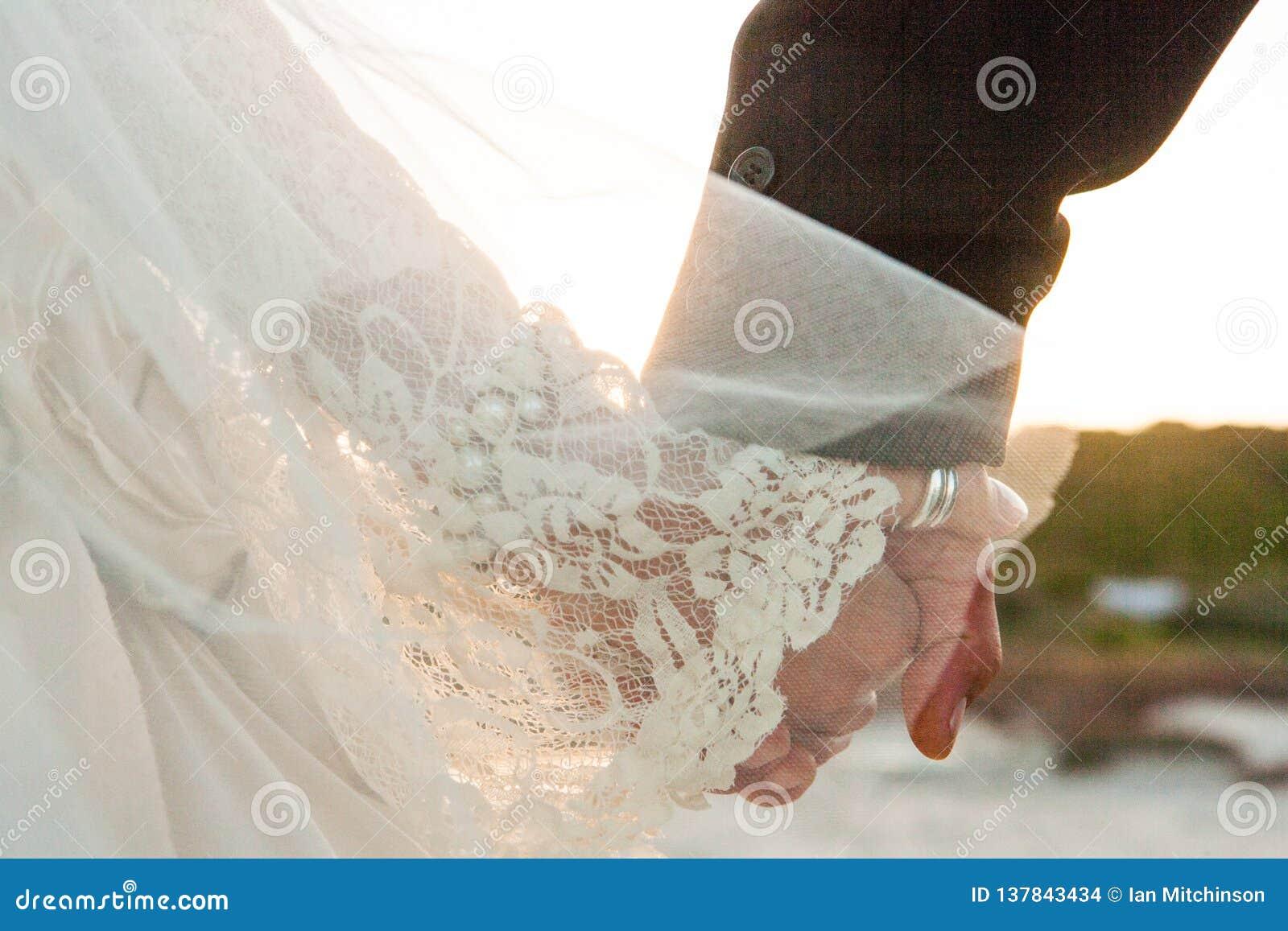 Des jeunes mariés avec des mains de prise de robe de mariage de cru marchant sur une plage vers le coucher du soleil