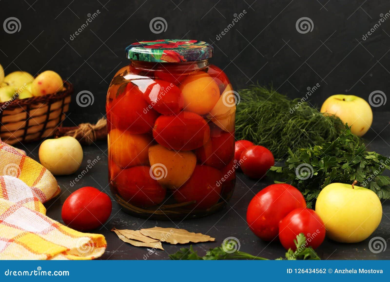 Des tomates marinées dans le pot sont situées sur un fond foncé