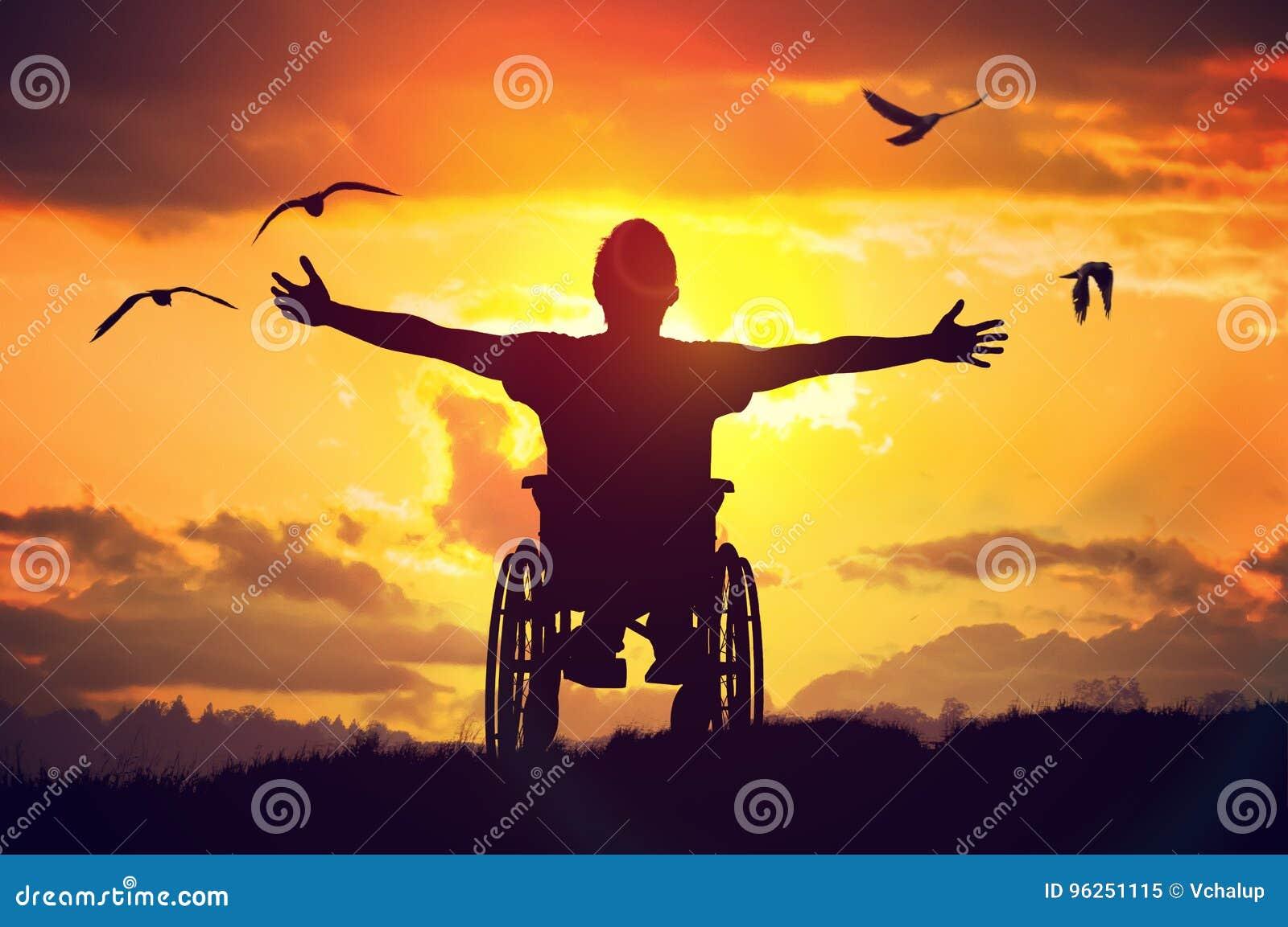 Desabilitou o homem deficiente tem uma esperança Está sentando-se na cadeira de rodas e está esticando-se as mãos no por do sol