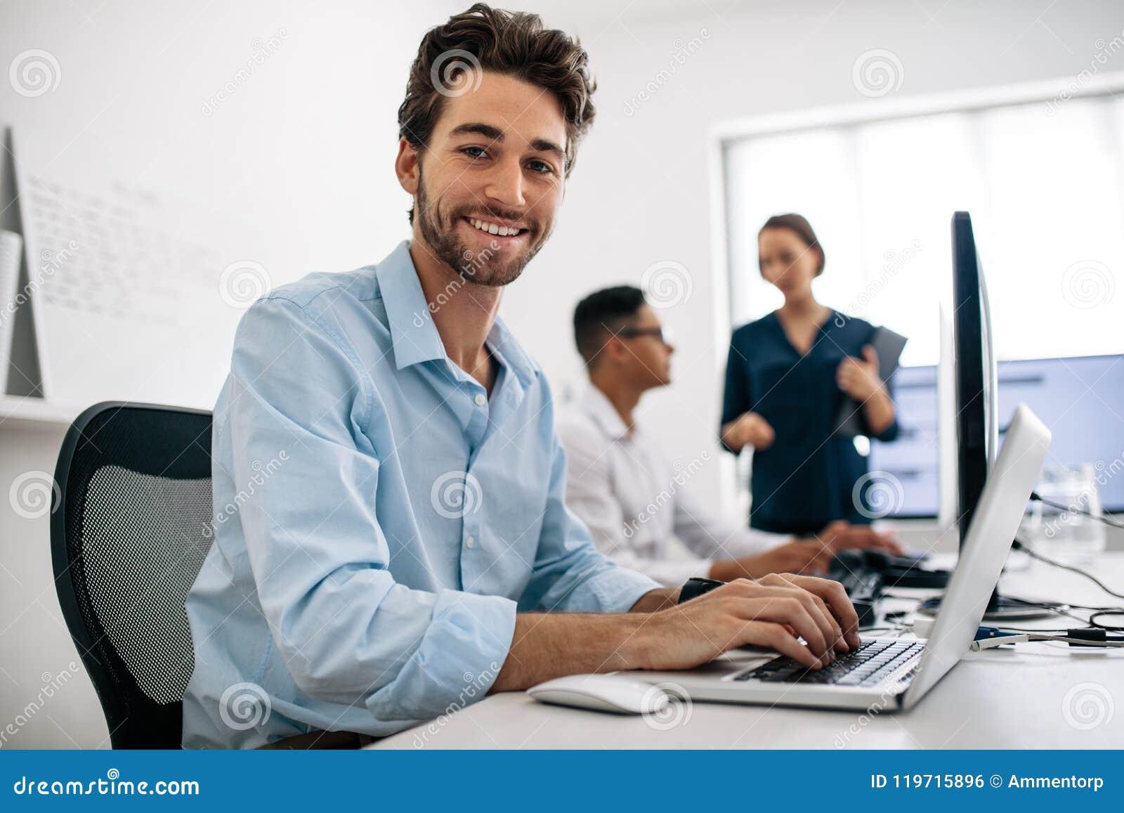 Desarrolladores de uso que trabajan en los ordenadores en oficina
