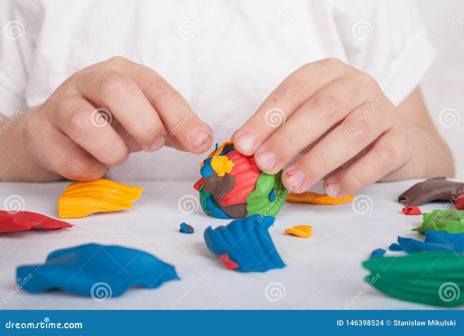 Desarrollo de las peque?as habilidades de motor de ni?os Un niño esculpe una bola colorida del plasticine