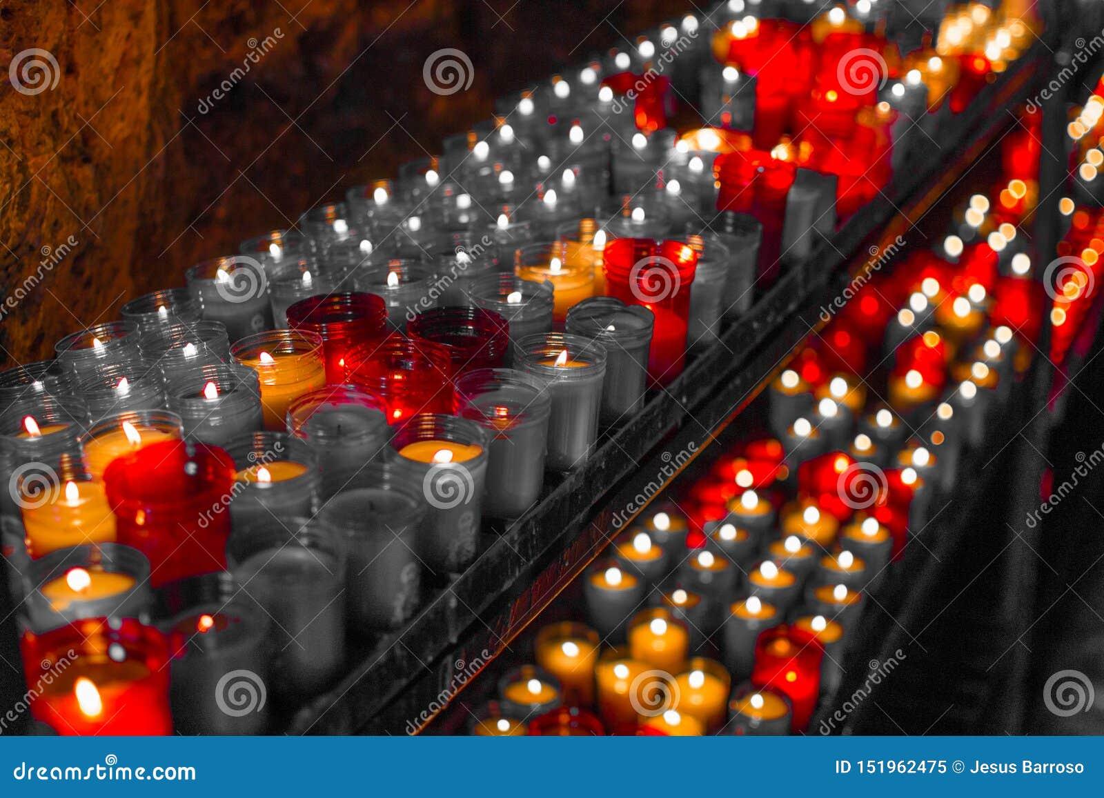 Desaturated roter Abschluss oben von bunten Kerzen in einer dunklen geistigen Szene Gedenken, Begräbnis, Denkmal Frommer Symbolis