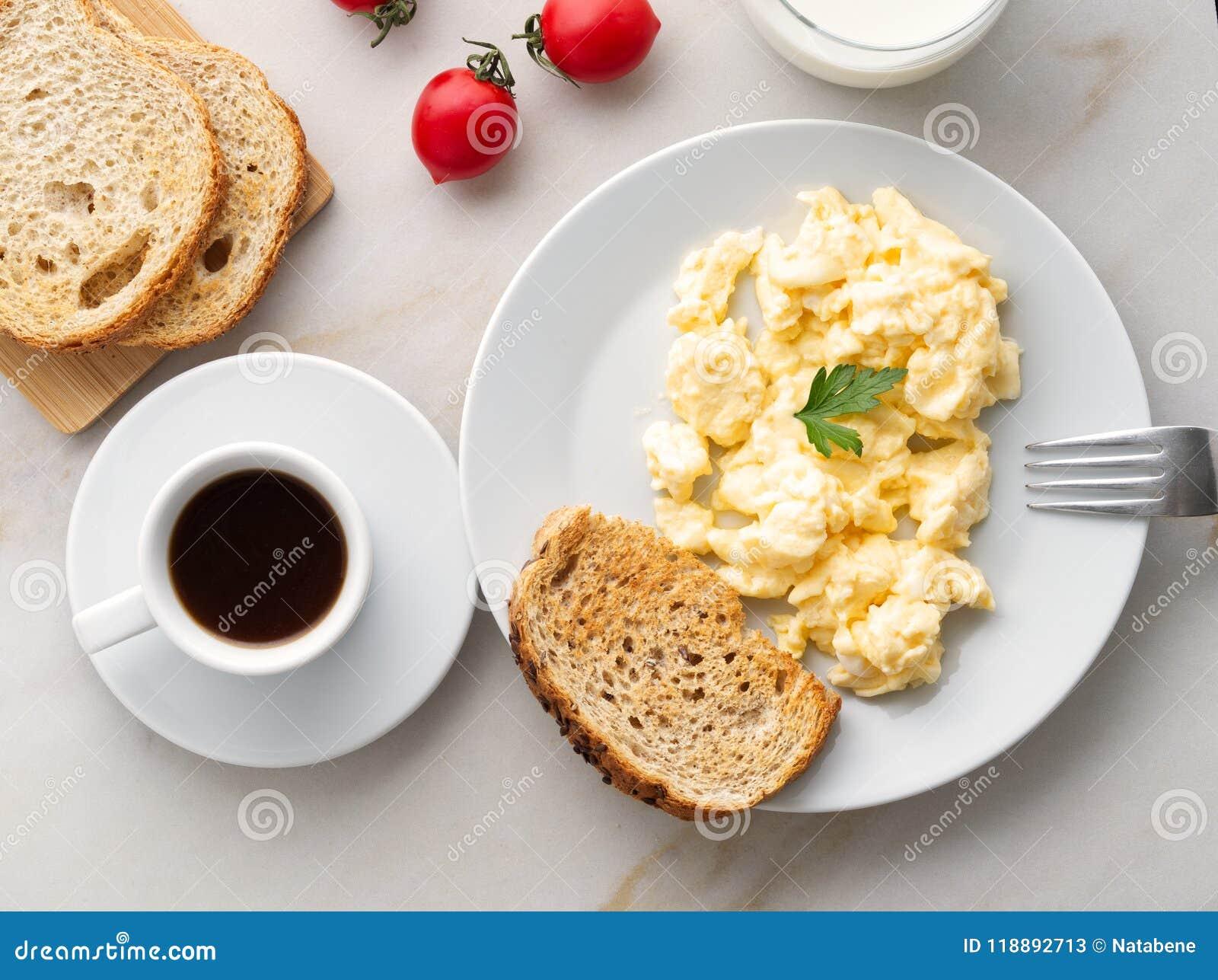 Desayune con los huevos revueltos cacerola-fritos, taza del café, tomates en el fondo de piedra blanco Tortilla, visión superior