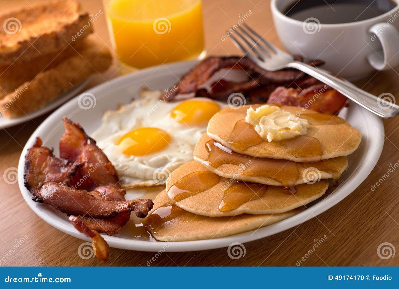 Desayune con tocino, huevos, las crepes, y la tostada