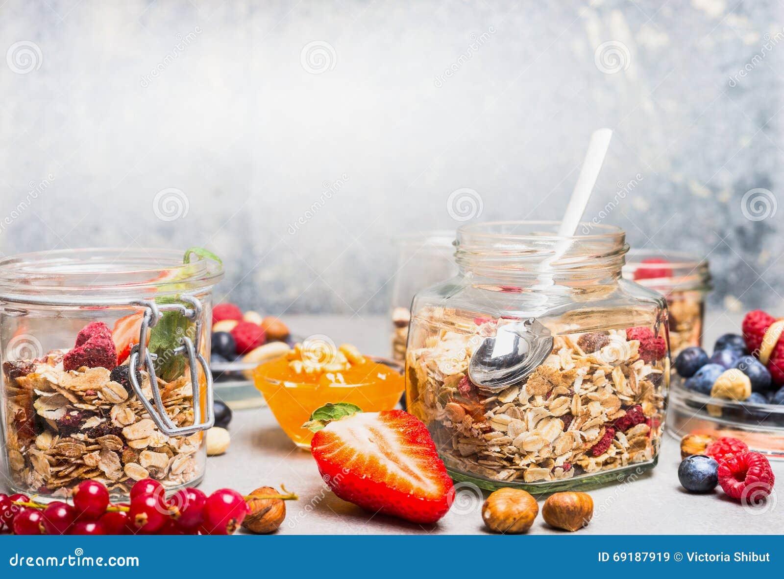 Desayune en los tarros de cristal con muesli, las bayas, las nueces y las semillas en fondo rústico ligero