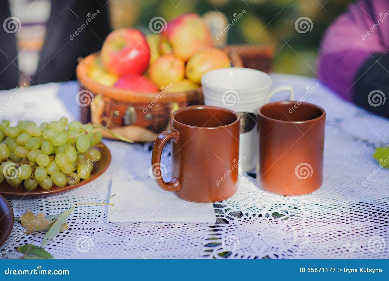 Desayuno, café, té y frutas apetitosos frescos en un mantel blanco blanco del cordón en una tabla en la calle