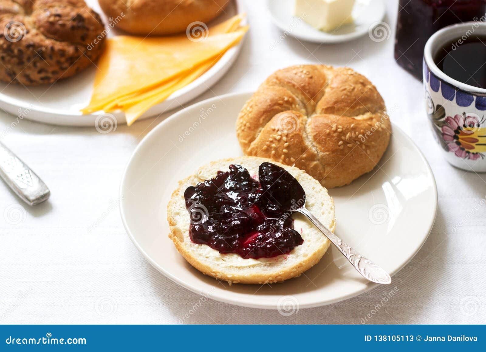 Desayuno con los rollos de Kaiser, atasco de la pasa, mantequilla y queso y té