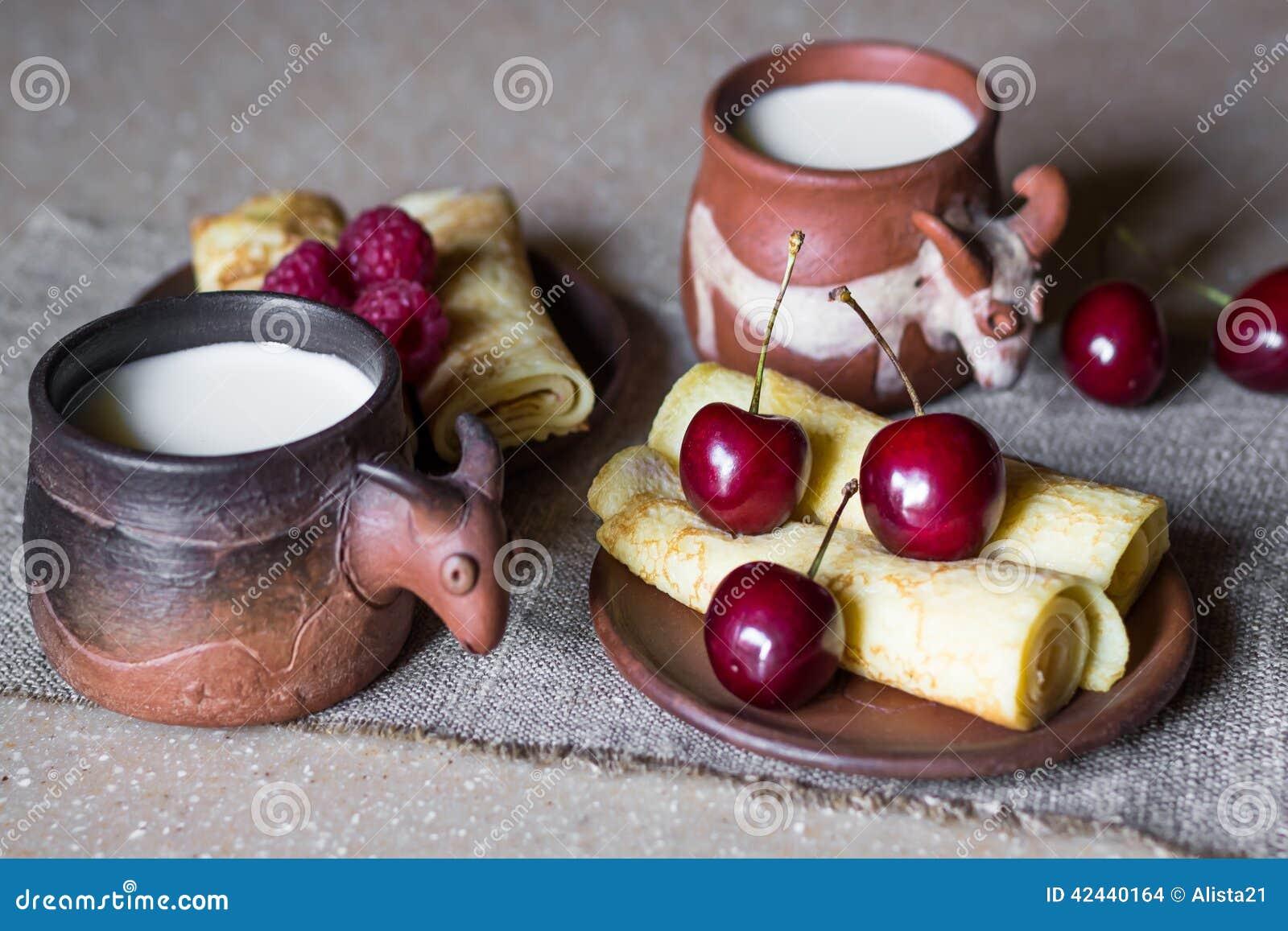 Desayuno de crepes rodadas con las bayas y la leche