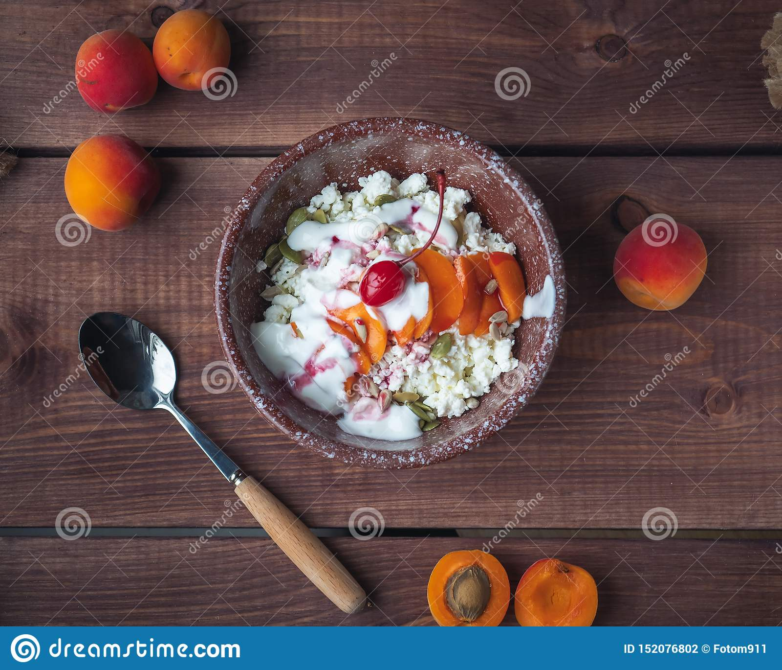 Desayuno del requesón con los albaricoques y las cerezas frescos en una placa de cerámica profunda en una tabla de madera, tomado