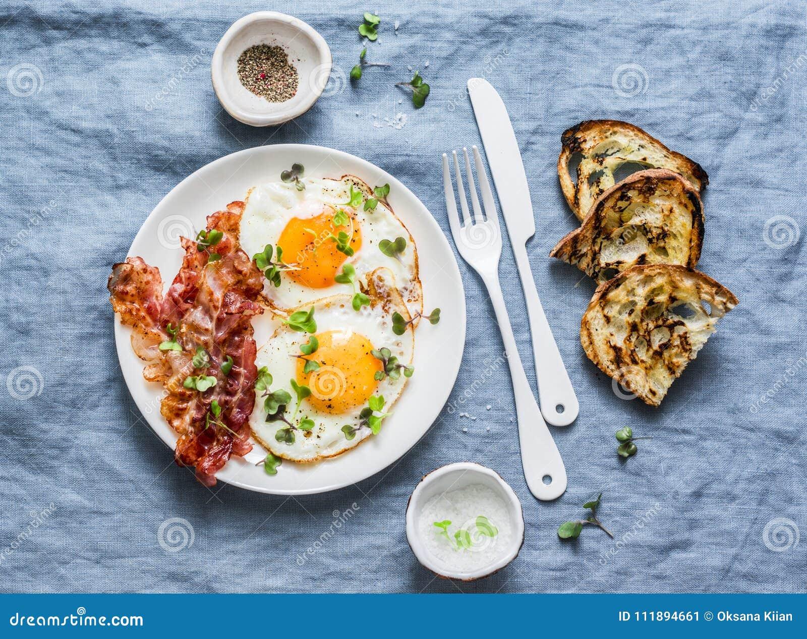 Desayuno o bocado tradicional - los huevos fritos, tocino, asaron a la parrilla el pan en el fondo azul, visión superior
