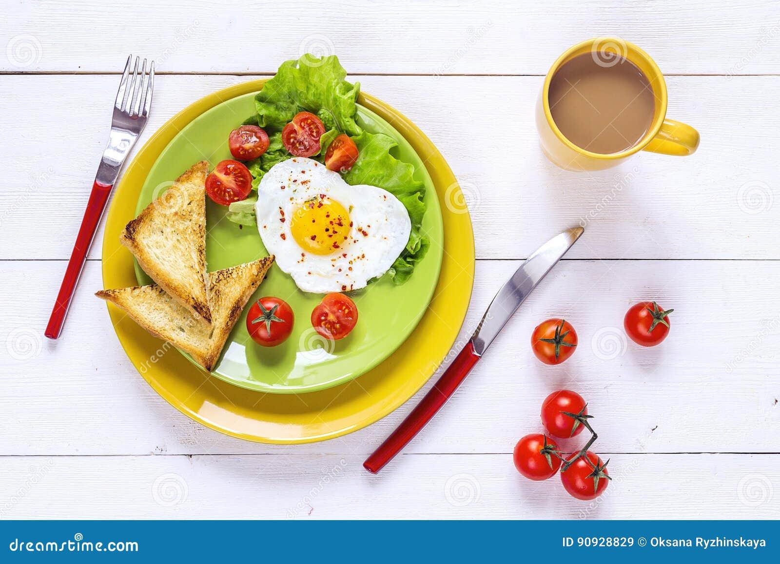 Desayuno sano con el huevo frito en forma de corazón, tostada, cereza tom