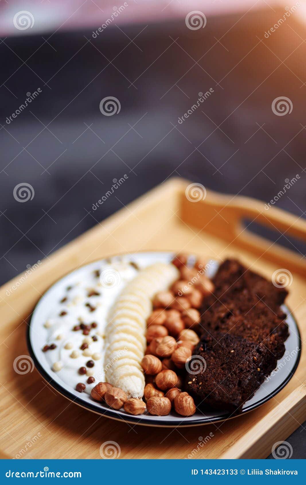 Desayuno sano con pan, el plátano, la avellana y el yogur deliciosos en cuenco
