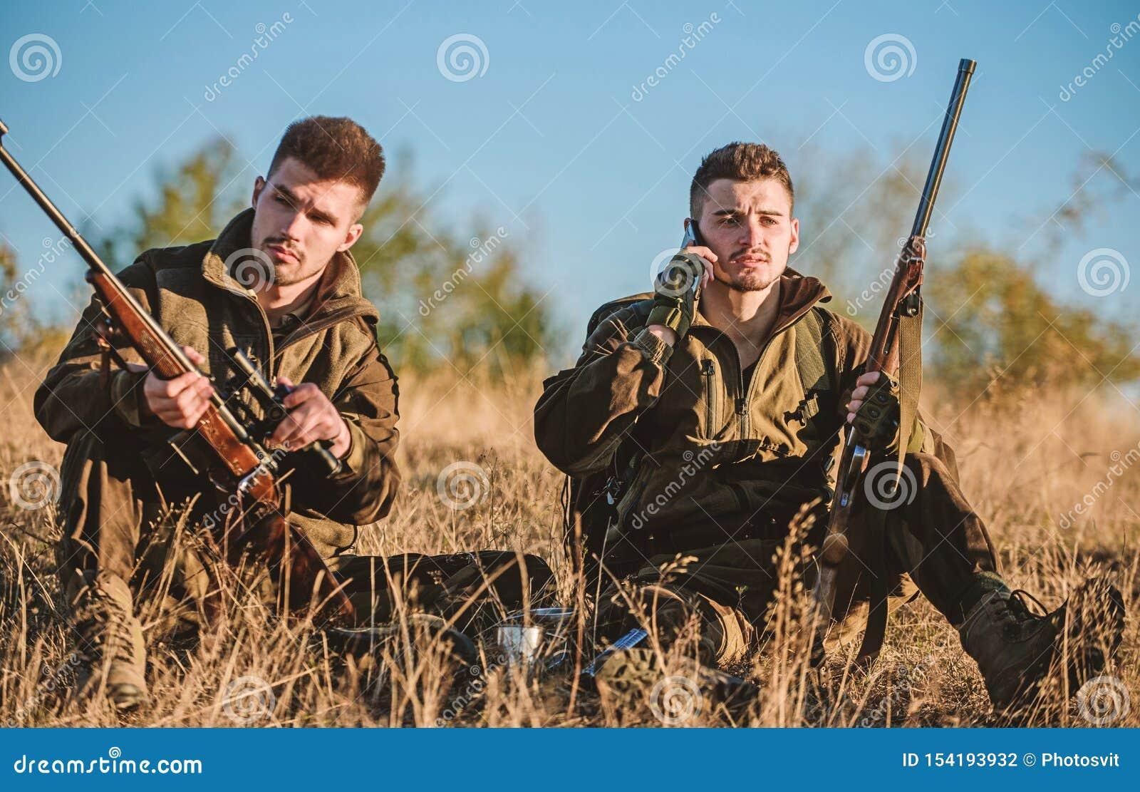 Descanse de verdad el concepto de los hombres Cazadores con los rifles que se relajan en el ambiente de la naturaleza Caza con oc