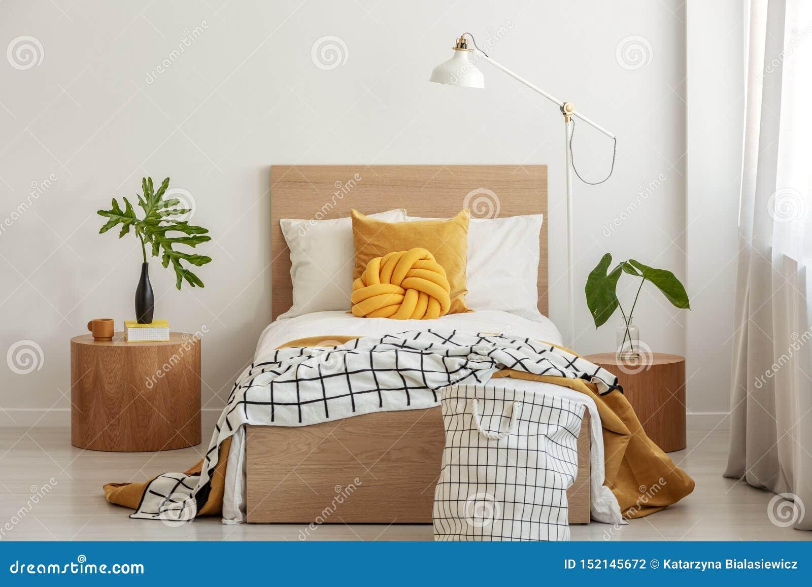 Descanso do nó e cobertura preto e branco na cama individual no interior elegante com a folha verde no vaso no nightstand de made