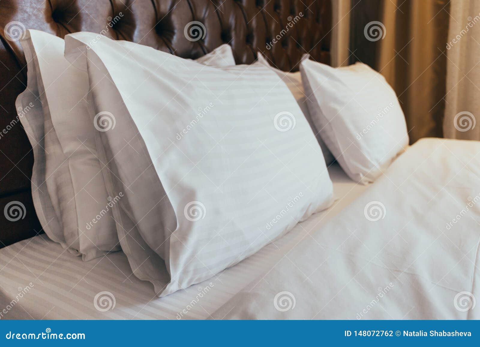 Descansos macios confort?veis na cama Folhas e descanso brancos do fundamento do close-up no fundo claro da sala da parede Concei