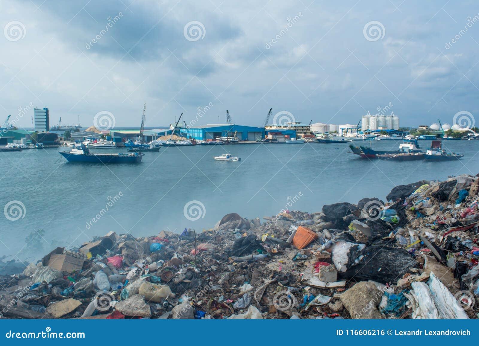 Descarga de lixo perto da vista para o mar completamente do fumo, da maca, de garrafas plásticas, de desperdícios e de lixo na il