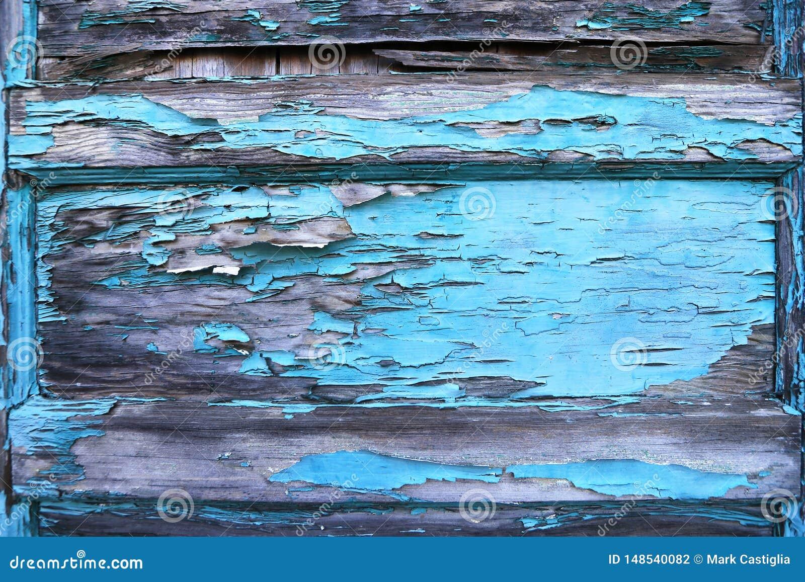 Descascando a pintura azul na porta de madeira velha Textura do fundo