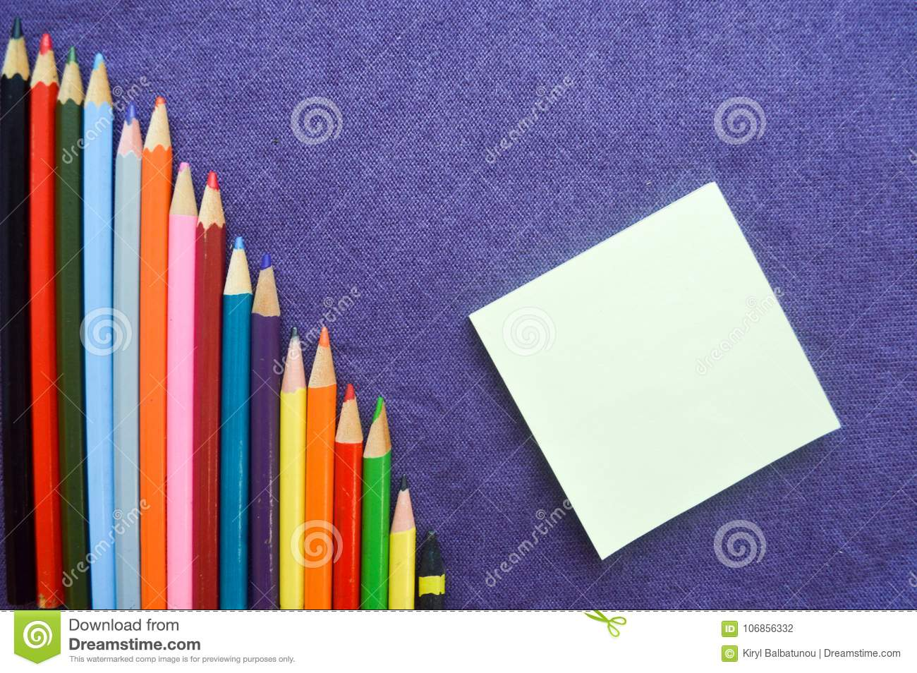 A descending chart of colorful, bright, variegated drawing pencils, a notebook