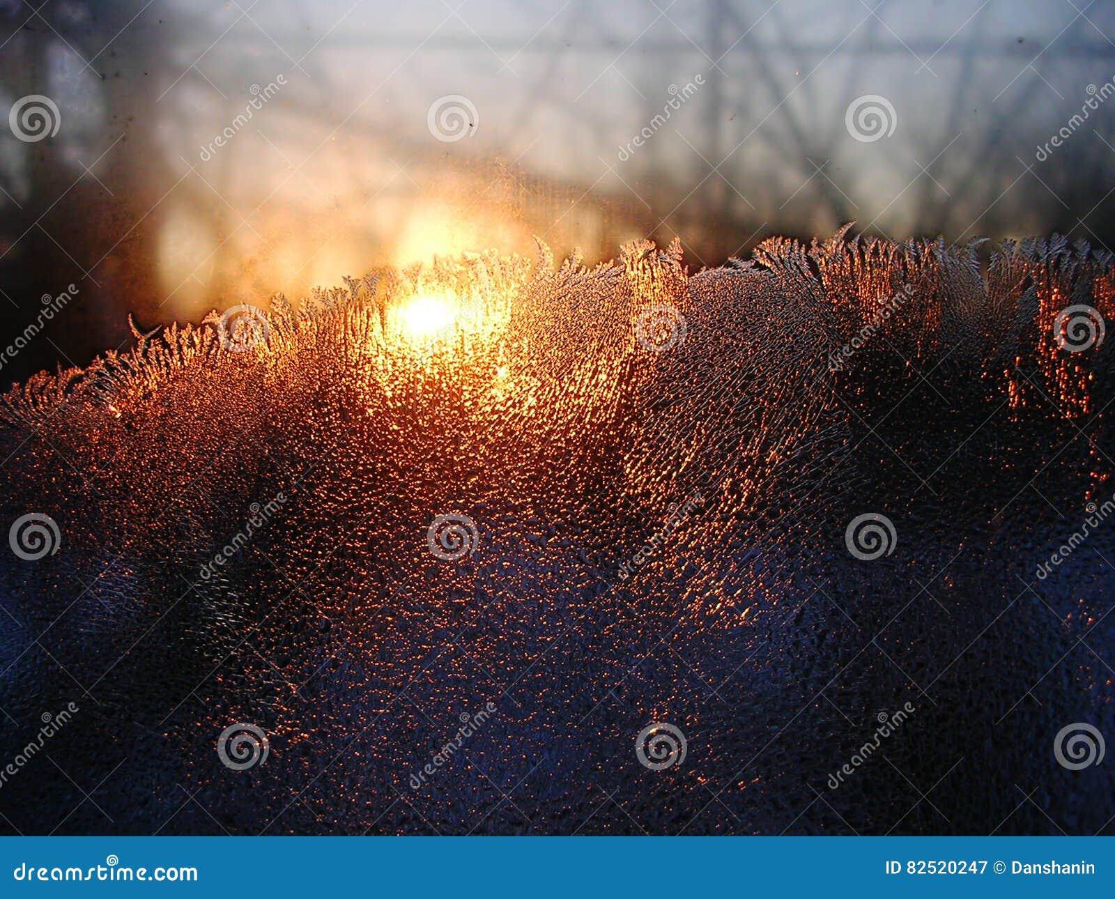 Descensos de los cristales y del agua de hielo de Frost en el vidrio de la ventana en el fondo de la salida del sol