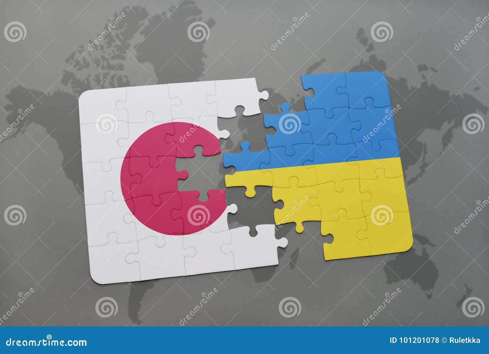 Desconcierte con la bandera nacional de Japón y de Ucrania en un fondo del mapa del mundo