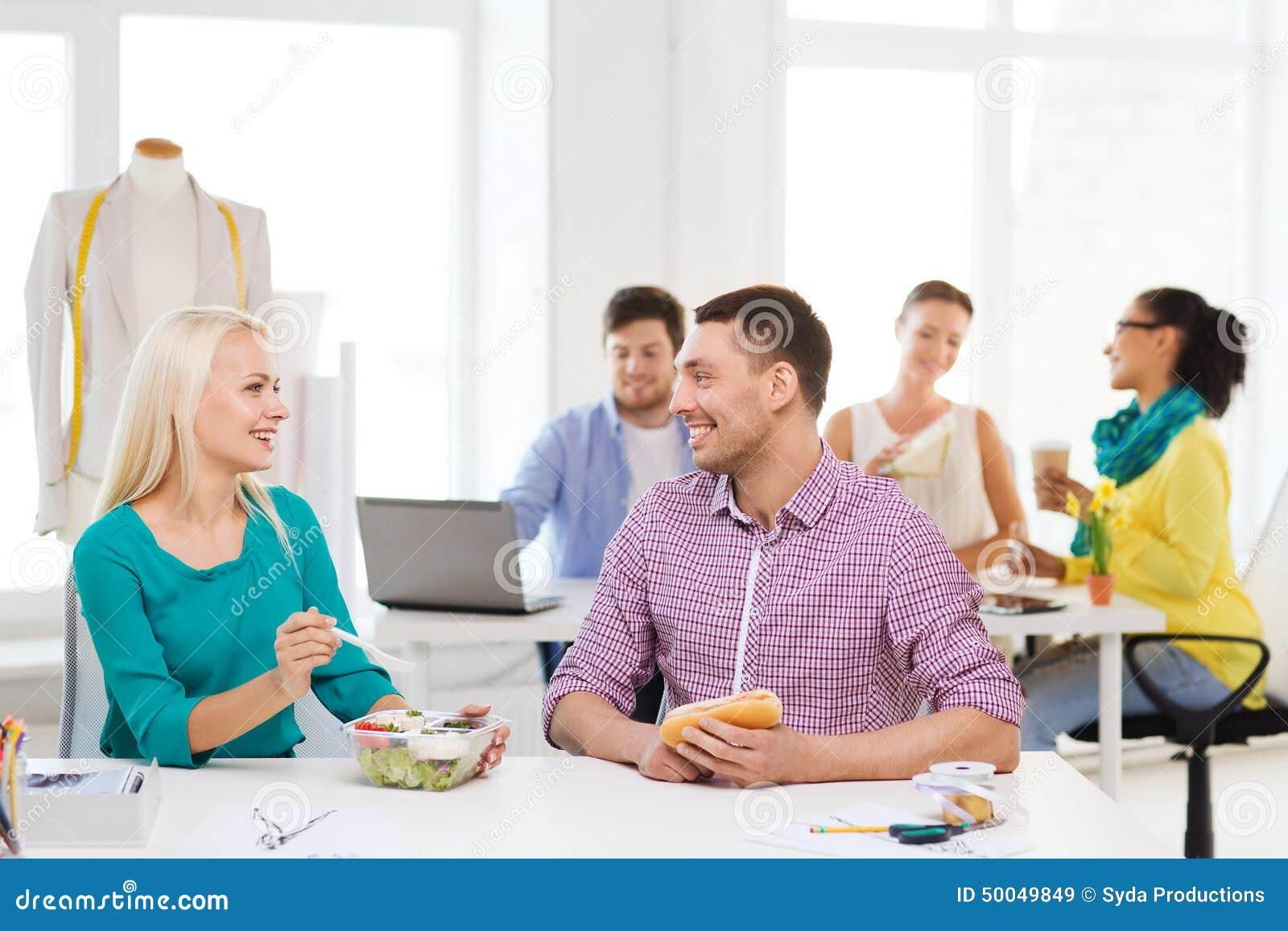 Desenhadores de moda de sorriso que têm o almoço no escritório