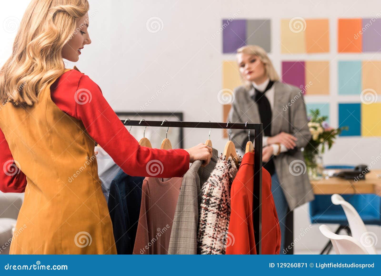 Desenhadores de moda que trabalham com roupa em moderno