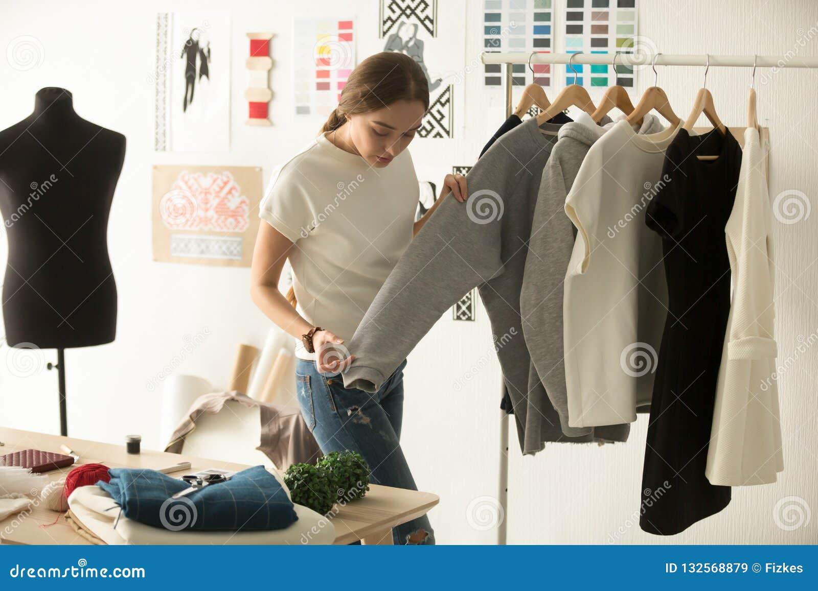 Desenhista de roupa fêmea que trabalha com desgaste de mulher novo na oficina