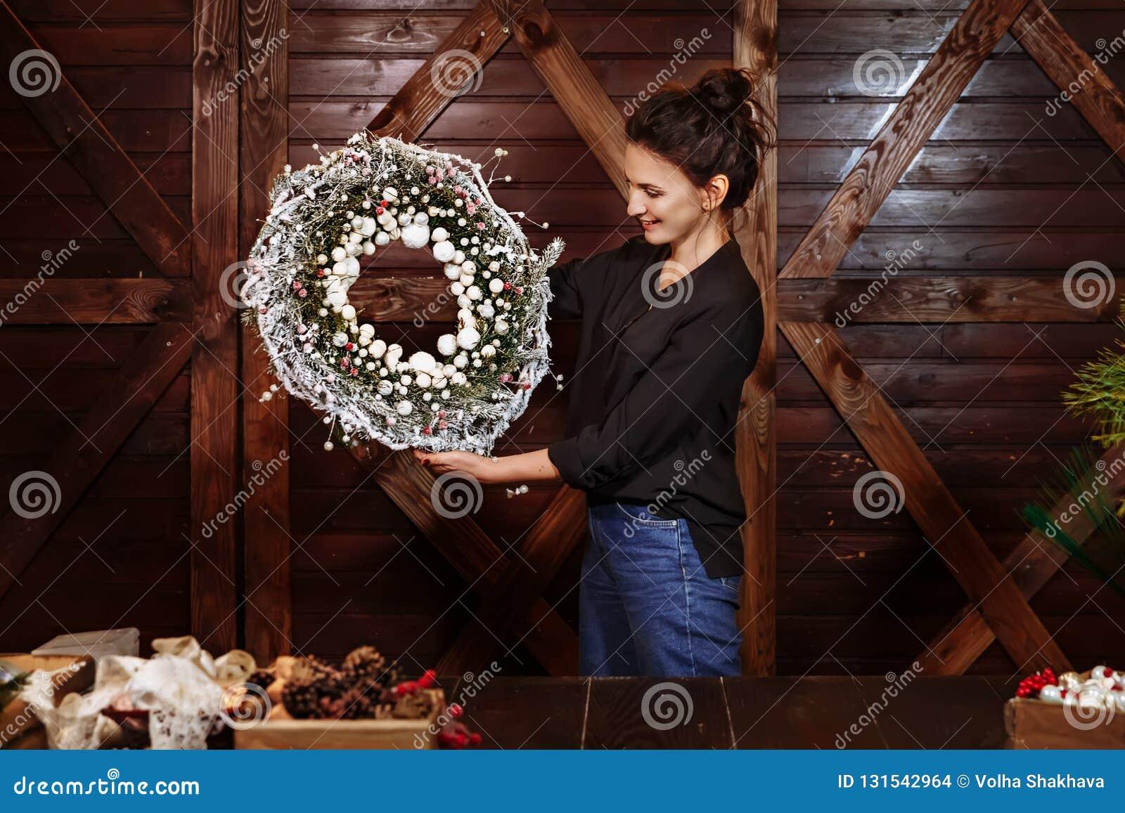 Desenhista de sorriso bonito que mostra a Natal a grinalda sempre-verde da árvore Jovem mulher que guarda a grinalda do Natal Gri
