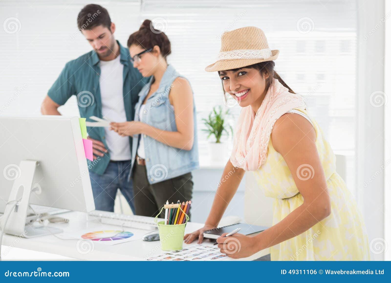 Desenhista de sorriso na frente dos colegas que usam a roda de cor