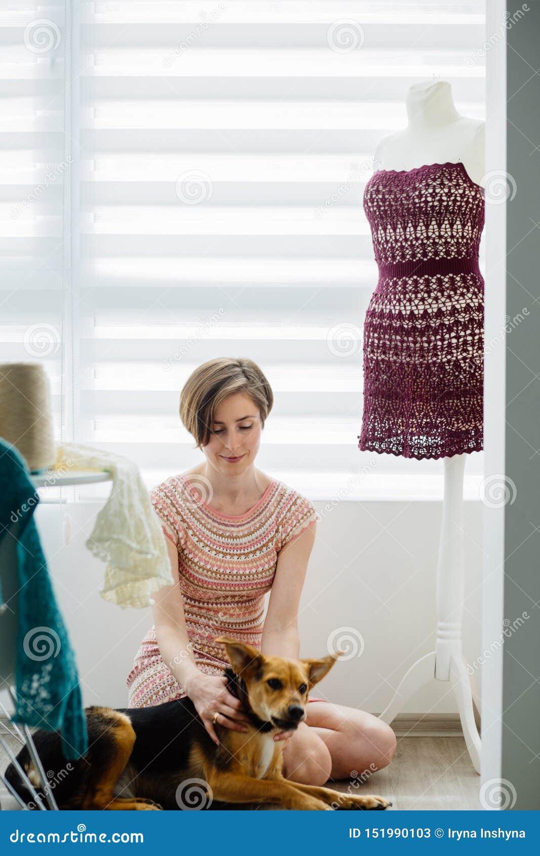 Desenhista fêmea novo da roupa que relaxa com seu cão Manequim próximo do vestido na casa acolhedor interior, estilo de vida autô
