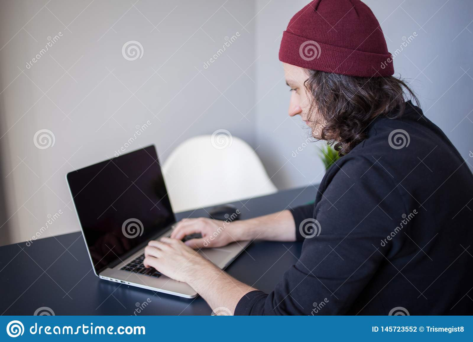 Desenhista para um portátil, um local de trabalho para freelancers Um homem novo que senta-se em uma tabela