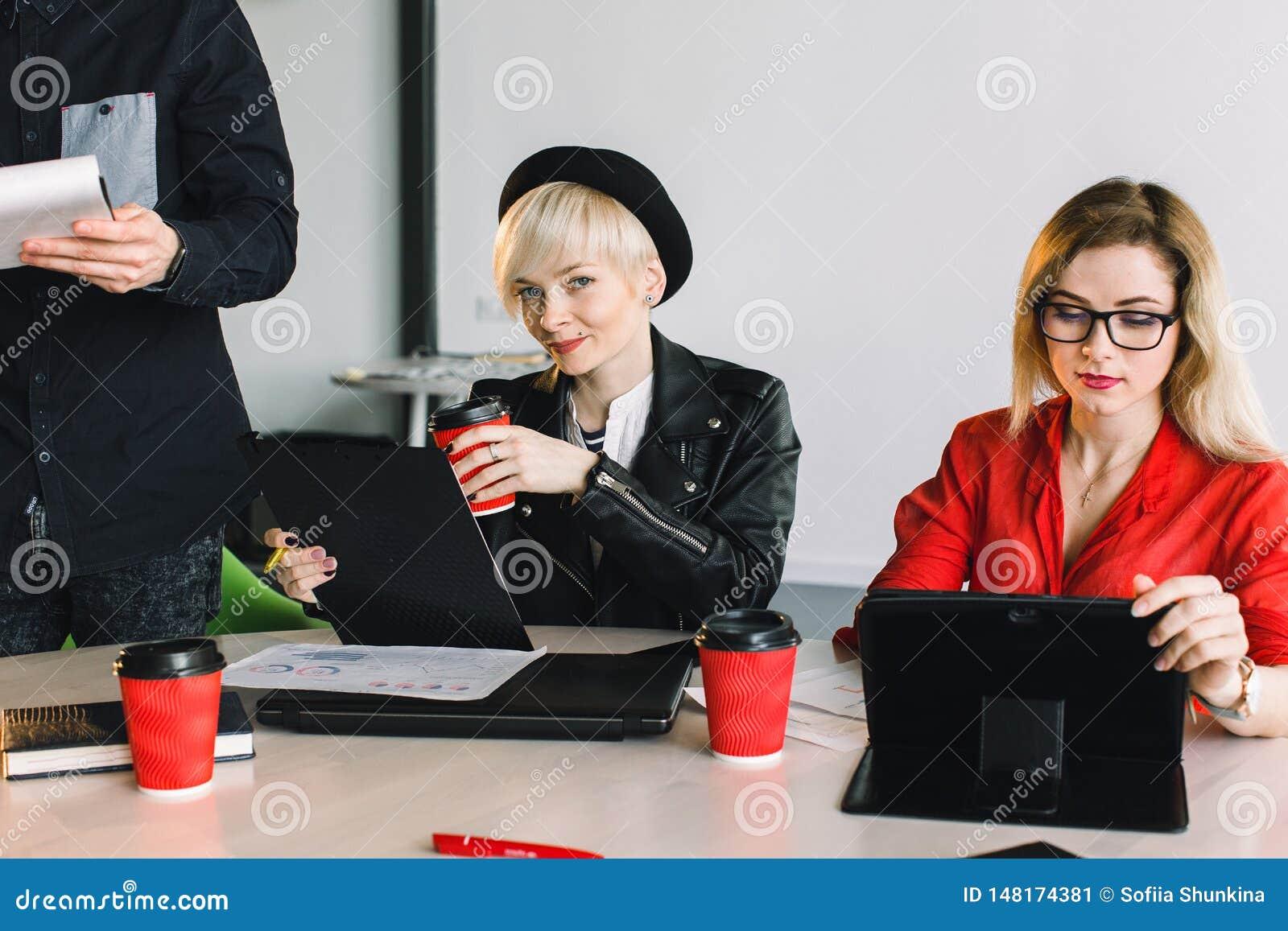 Desenhistas felizes que trabalham junto em seu escrit?rio Dois colegas de trabalho das moças que sentam-se na tabela e que trabal