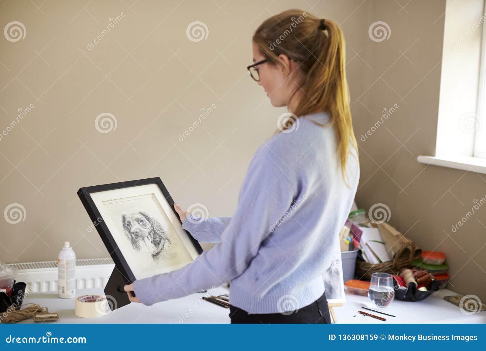 Desenho adolescente fêmea de Holding Framed Charcoal do artista do cão no estúdio