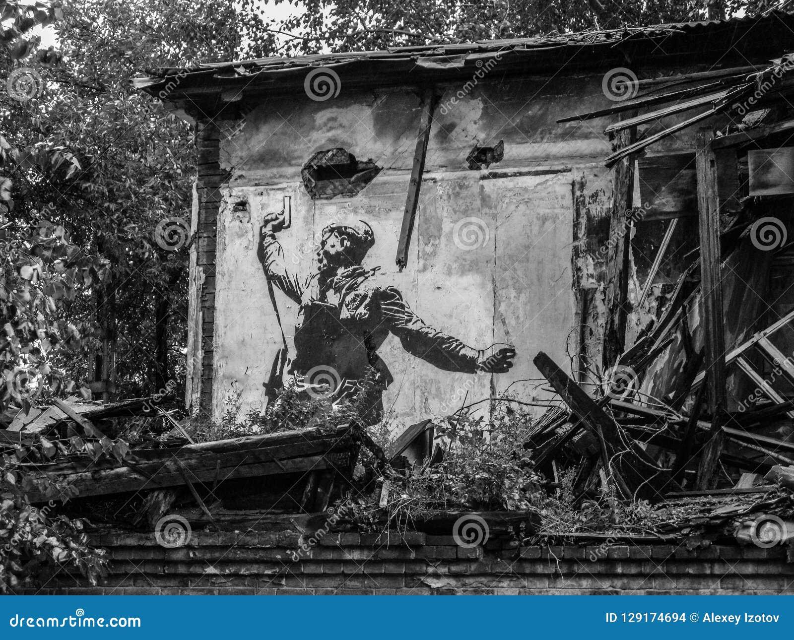Desenho de um soldado do russo com uma arma na parede das ruínas