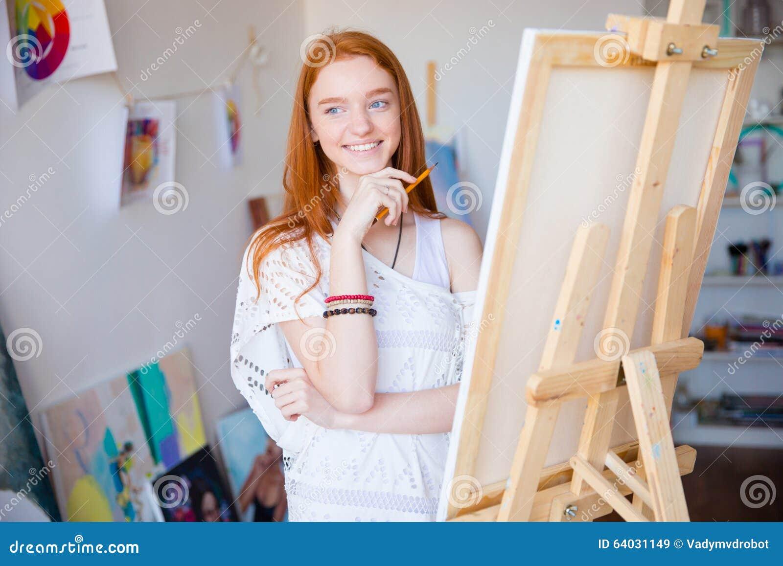 Desenho fêmea inspirado feliz do artista com o lápis na classe de arte