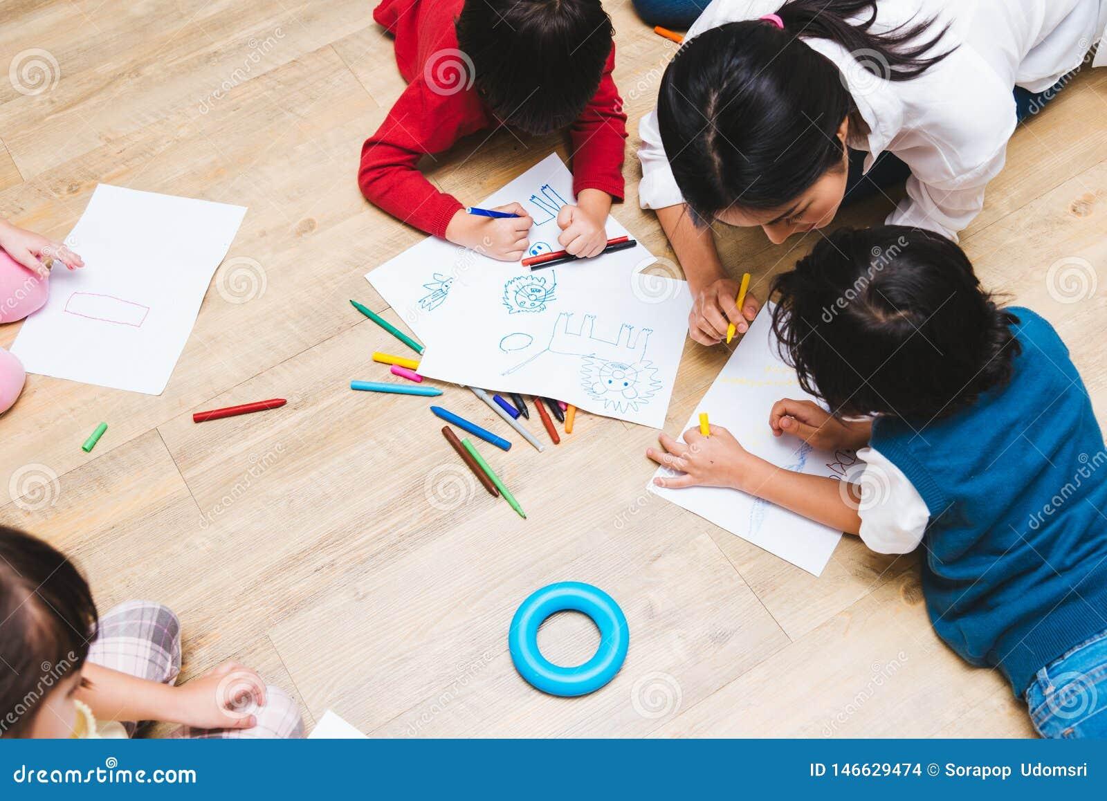 Desenho feliz da pintura do jardim de inf?ncia do menino e da menina da crian?a do grupo das crian?as da fam?lia da vista superio