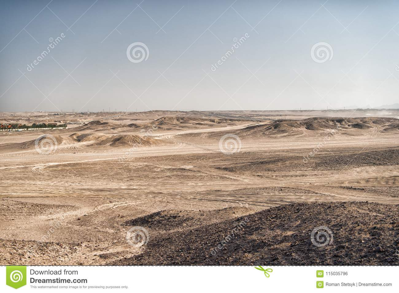 Desert landscape on clear blue sky background. Dune land with dry terrain surface. Ecology and global warming effect. Hopelessness