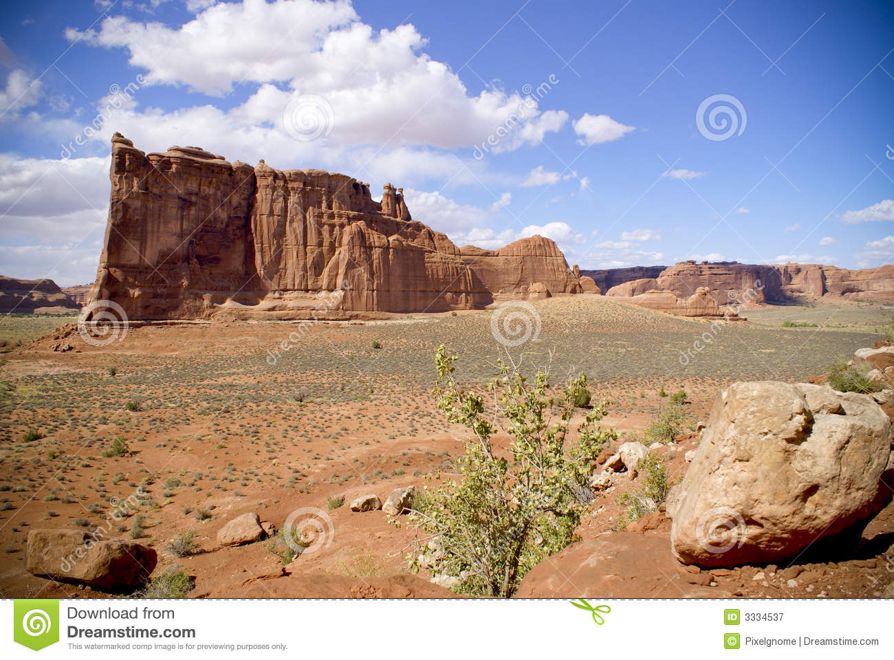 view across dry desert to abrupt rock formations often called mesas ...