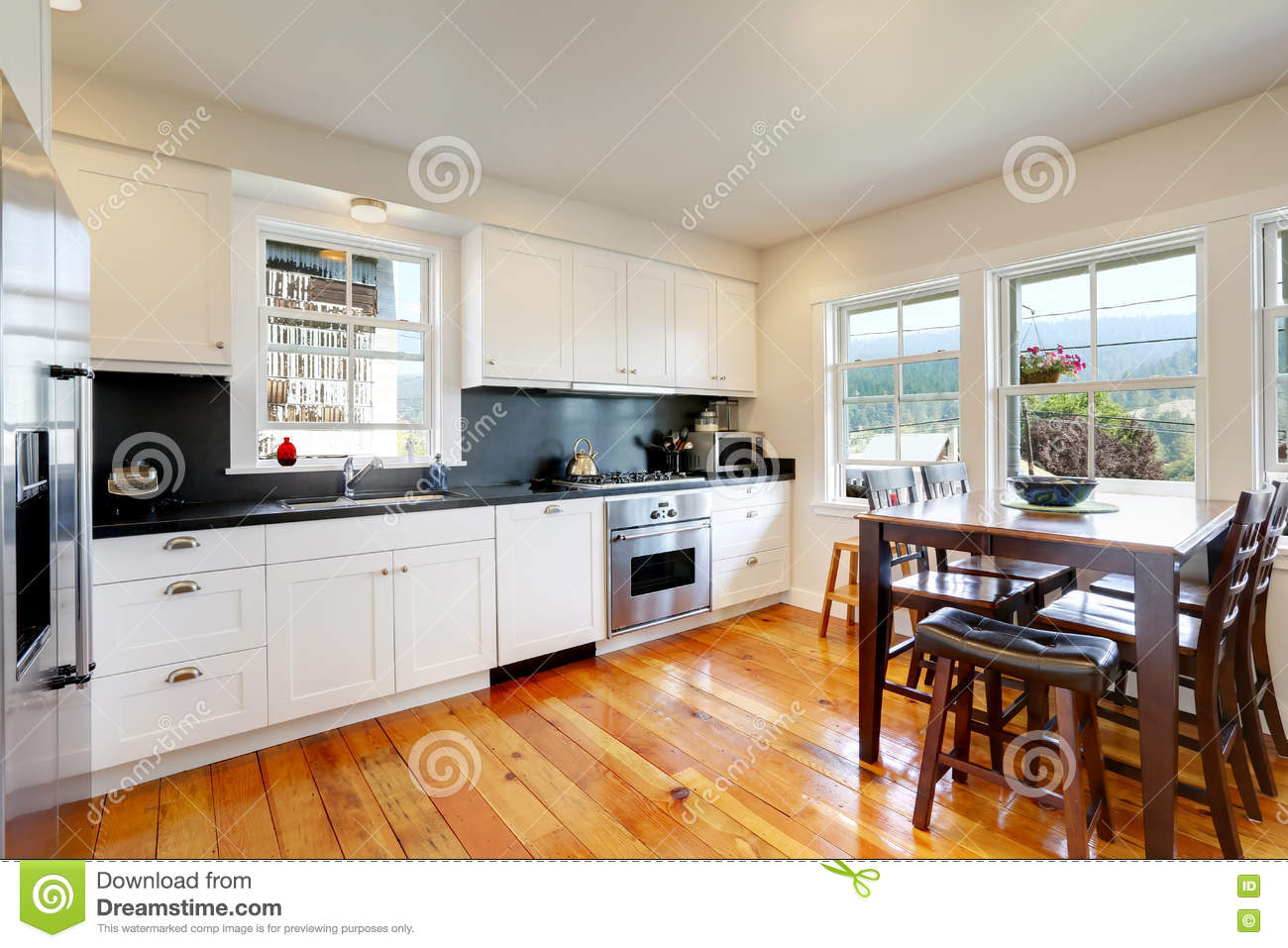 Design Of Kitchen Room Interior With White Cabinets And Black Counter Tops Tall Wooden Dining Table Chairs Northwest USA
