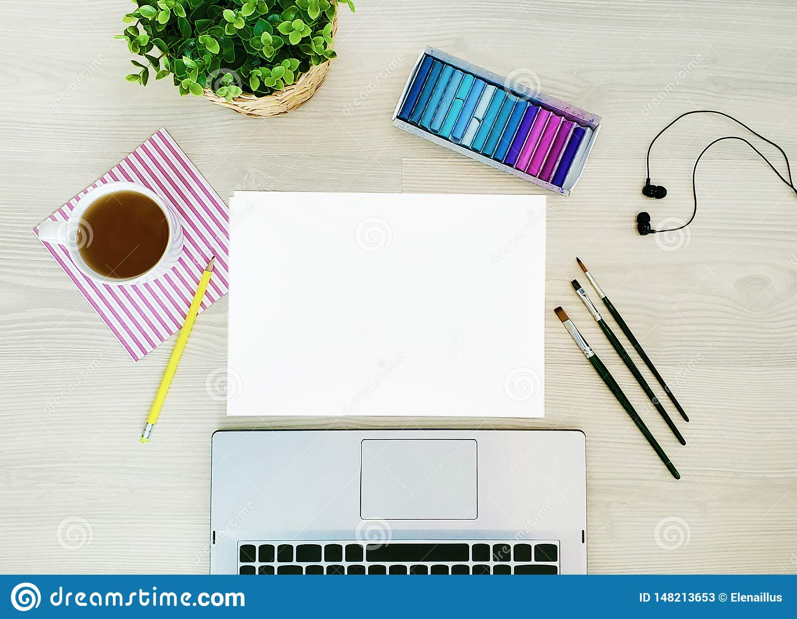 Designer, artist workplace. Creative, trendy,artistic mock up with paper, coffee,notebook or keyboard, earphones, a yellow pencil.